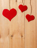 Handmade hearts hanging on line against wood-grain wall Royalty Free Stock Images
