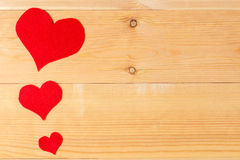 Handmade hearts hanging on line against wood-grain wall Stock Photography