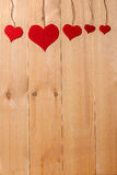 Handmade hearts hanging on line against wood-grain wall Royalty Free Stock Photos