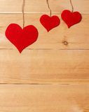Handmade hearts hanging on line against wood-grain wall Royalty Free Stock Image