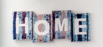 Handmade HOME sign. Wooden colorful planks over white wall background. Rustic decor Stock Image