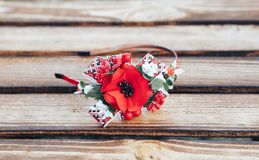 Handmade hoop flowers. Red poppies hair band on wooden background. Ukrainian style. Ukrainian ornament stock photography