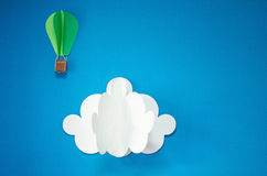 Handmade hot air balloon and cloud in the sky. Paper art style. Isolates on blue background. royalty free illustration