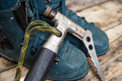Handmade ice axe with old boots on wood background Royalty Free Stock Images