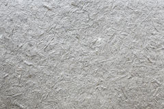 Handmade japanese paper texture with fibers. Grey handmade japanese paper texture with fibers of hay and gras royalty free stock images