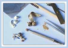 Handmade Jewellery Crafting Equipment on Soft Blue Background. The tools and equipment used to make homemade ceramic jewellery Royalty Free Stock Photography