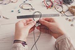 Handmade jewelry making, female hobby. Woman creating bracelet at home workshop, artisan pov. Fashion, handicraft concept royalty free stock photo