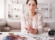 Handmade jewelry making, female hobby. Young woman creating bracelets at home workshop. Fashion, handicraft concept royalty free stock photo