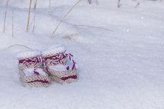 Handmade knitted baby booties in snow. Background with handmade knitted baby booties of warm wool in winter sunlight Royalty Free Stock Photo