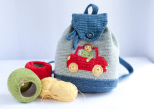 Handmade knitted backpack and colorful tangles of yarn Royalty Free Stock Image