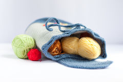 Handmade knitted backpack and colorful tangles of yarn Royalty Free Stock Photography