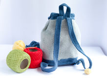 Handmade knitted backpack and colorful tangles of yarn Royalty Free Stock Photos