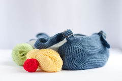 Handmade knitted backpack and colorful tangles of yarn Stock Photos