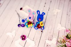 Handmade knitted bunny rabbits and artistic decorations on wooden table background Stock Images