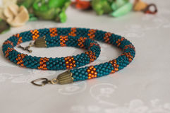 Handmade knitted necklace from beads on a textile background Stock Photos
