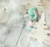 Handmade knitted rabbit. Christmas Bunny in a scarf and hat with a large pumpon among the decorative Christmas trees and balls. Christmas composition Royalty Free Stock Images