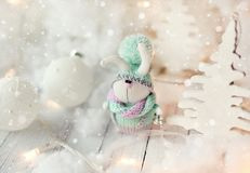 Handmade knitted rabbit. Christmas Bunny in a scarf and hat with a large pumpon among the decorative Christmas trees and balls. Christmas composition Stock Photo