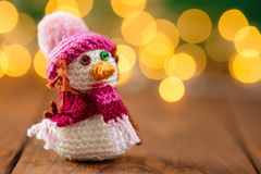 Handmade knitted snowman toy on wooden background with bokeh. Handmade crochet snowman toy on wooden background with garland lights bokeh. Christmas still life Stock Image