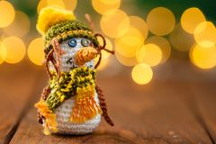 Handmade knitted snowman toy on wooden background with bokeh. Handmade crochet snowman toy on wooden background with garland lights bokeh. Christmas still life Stock Photos