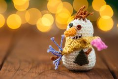 Handmade knitted snowman toy on wooden background with bokeh. Handmade knitted snowman toy on wooden background with garland lights bokeh. Christmas still life Royalty Free Stock Photo
