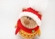 Handmade knitted toy. Knitted bear close-up in color sweater and red hat with white pompom on white background. Handmade knitted toy. Knitted bear close-up in Stock Photos