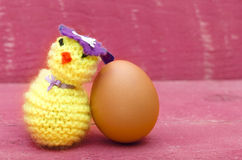 Handmade knitted woolen Easter chicken with real egg on pink woo Royalty Free Stock Images