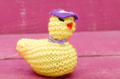 Handmade knitted woollen Easter chicken on pink wooden backgroun Stock Photos