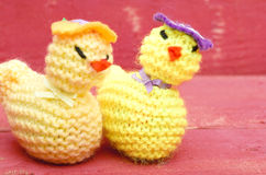 Handmade knitted woollen Easter chicks on pink wooden background Royalty Free Stock Photography