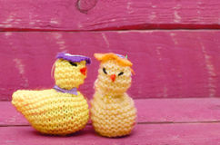 Handmade knitted woollen Easter chicks on pink wooden background Royalty Free Stock Photos
