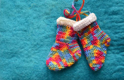 Handmade knitting socks with ornament hanging on ribbon. Christmas handmade decorations. Christmas colored boots in anticipation o Stock Images