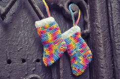 Handmade knitting socks with ornament hanging on ribbon. Christmas handmade decorations. Christmas colored boots in anticipation o Stock Photography