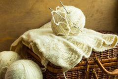 Handmade knitwear, clew of white wool yarn on vintage hobby and crafts wicker chest, wool clews, wood table, cozy atmosphere. Shabby chic style stock images
