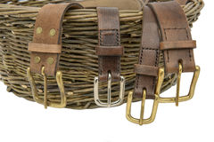Handmade Leather Belts. With metal buckles arranged over a hand woven willow basket stock images