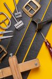 Handmade leather craft tools, belt buckle and black leather straps on yellow background.  royalty free stock photo