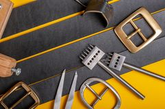 Handmade leather craft tools, belt buckle and black leather straps on yellow background.  royalty free stock image