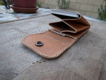 Handmade leather wallet. In wooden table in terrace stock image