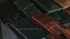 Handmade leather wallets for sale in the family shop. Many wallets on a wooden table stock footage