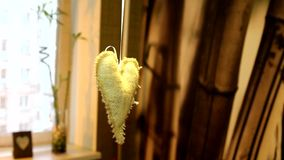 Handmade linen heart decoration in the interior apartments. Handmade. Hanging decorations in the form of heart. It is made of burlap and decorated with beads and stock video footage