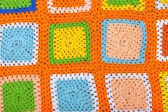 A handmade crochet wool blanket. A handmade multicolored crochet wool blanket background or texture stock photography