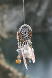 Handmade native american dream catcher on background of rocks Stock Images