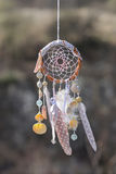Handmade native american dream catcher on background of rocks an Stock Image
