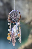 Handmade native american dream catcher on background of rocks an Royalty Free Stock Image