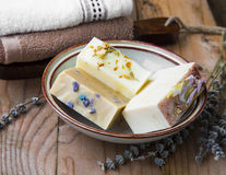Handmade natural soap with floral extracts and goat milk ingredi. Ents on wooden background Royalty Free Stock Photography