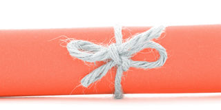 Handmade natural string node tied on orange paper scroll  Stock Photos