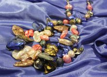 Handmade necklace of colored mother of pearl on a blue background. royalty free stock photography