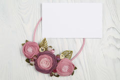 Handmade necklace with pink colored flowers lying on a white wooden background and letter with congratulation Stock Images