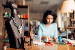 Handmade necklace on wooden mannequin, needlework. Handmade necklace on a wooden mannequin, needlework. Female craftman at the workplace on background Stock Photography
