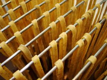 Handmade noodles hanging on wire rack to dry Royalty Free Stock Image
