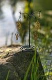 handmade Ohrringe mit Gängen auf dem Stein am sonnigen Tag Stockfotografie