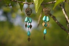 handmade Ohrringe mit Steinen und goldene Herzen auf dem Baumast Stockfotografie
